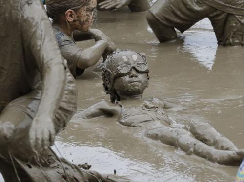 小朋友在泥巴里玩漂浮。