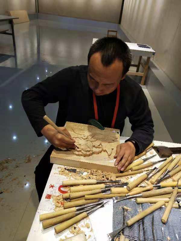 """创作中的韩伟 经过激烈的比赛,包头市特殊教育学校的聋人教师——韩伟的木雕作品""""牡丹""""在本次大赛中勇夺桂冠。"""